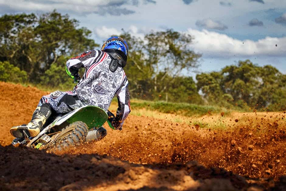 A man flying through the air while riding a bike down a dirt road