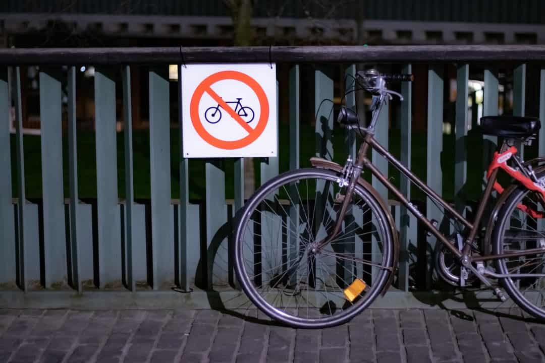 A bicycle is parked near a fence