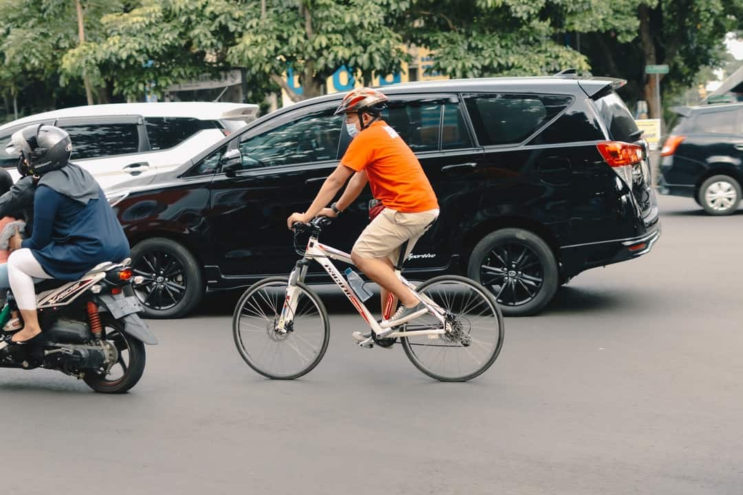 A person riding a bicycle in a parking lot